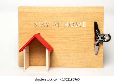 Wall decoration with paper holder clipboard and a house shape made from wood isolated on white background. Written message 'Stay At Home' concept photo during Covid-19 pandemic.