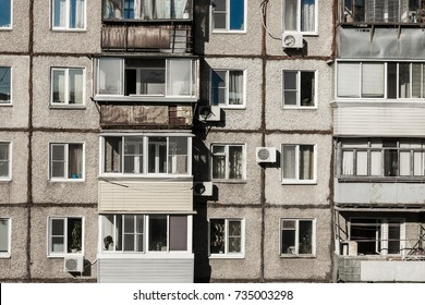 The wall of a dilapidated apartment building, windows and old balconies. A terrible condition of housing, bad conditions, cheap apartments.