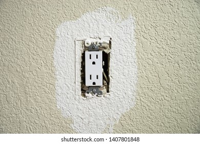 wall electrical outlet with the cover off being painted on a textured wall