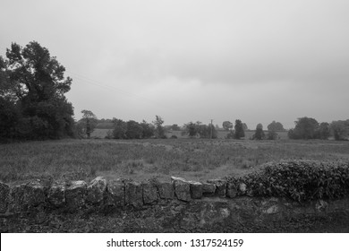 A wall with field in the background - County Laois, Ireland - black and white