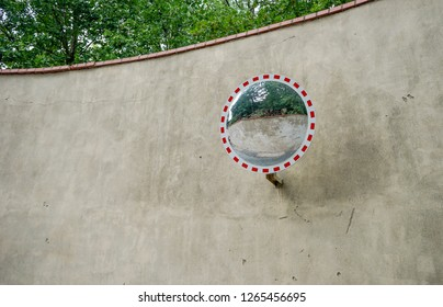 Wall in front of green trees with a round mirror