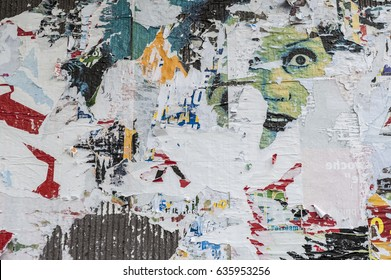 Wall full of Scraped posters with printed a visible female face.