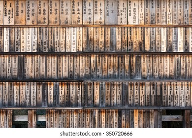 Wall full of weathered wood boards (ema) with the names of the donors and dates at the entrance of the Fushimi Inari Shrine in Kyoto, Japan.