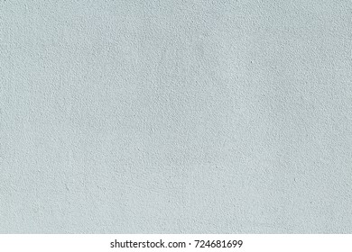 Wall grungy covered with plaster and painted white. Clean surface with pimples, small bumps and stripes. Flat wall of the building.