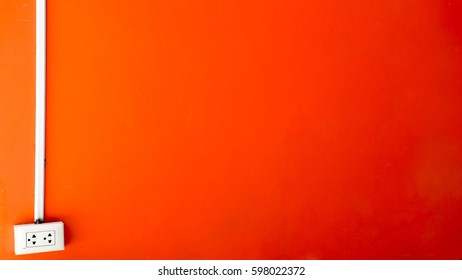The wall has orange color and a plug