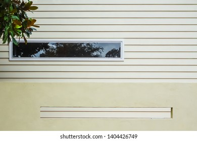 Wall of house and fence with parallel narrow wide windows