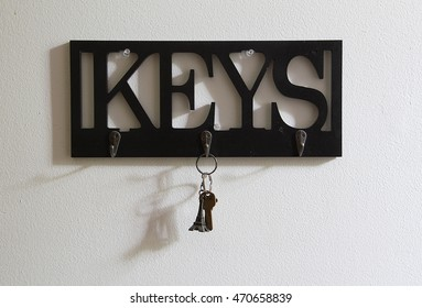 Wall key holder in light and shadow with a set of keys hanging from it.