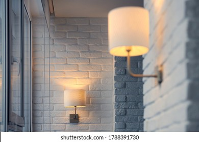 Wall lamp in modern loft apartment. Wall sconce on white brick wall. Yellow lights in shade. Evening, lights on.