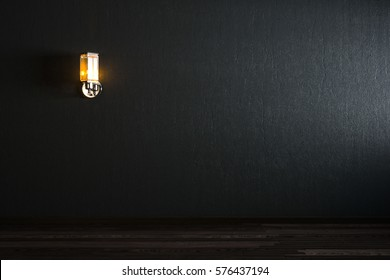 The wall lamp on the black wall. working space