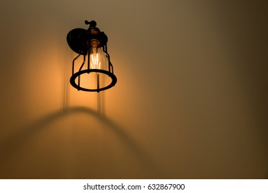 Wall lamp with yellow shade on cement wall.