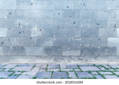 The wall with light gray, white bricks and cobblestone sidewalk decoration for background.
