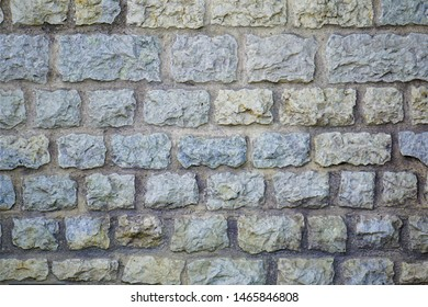 Wall of limestone bricks hand cut hewn set with mortar Gray beige sand colored with discoloration between staggered rocks.  Roman amphitheater building materials natural resource mined historically