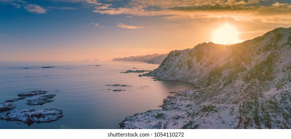 The wall of Lofoten stretching into the horizon, with the islands of Mosken and Værøy in the distance. Steep mountains covered in snow going straight into the ocean.