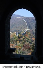 Wall from loophole. View from the window (loophole) on the great wall of China. Masonry, autumn trees.