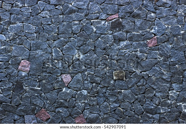 Wall made of black rough stone close up