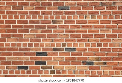 The wall made by red, brown, gray and black bricks