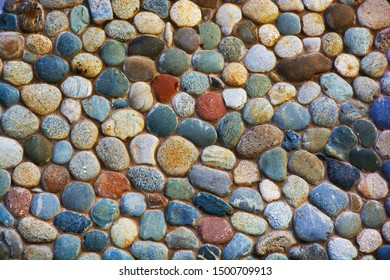The wall is made of colored round stones.