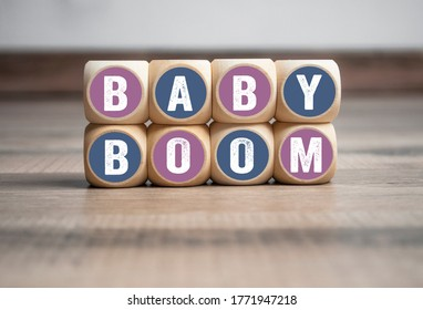 Wall made of cubes and dice with word baby boom on wooden background