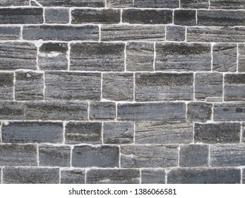 Wall made from grey and black old Coquina bricks from the 1700s in St Augustine Florida