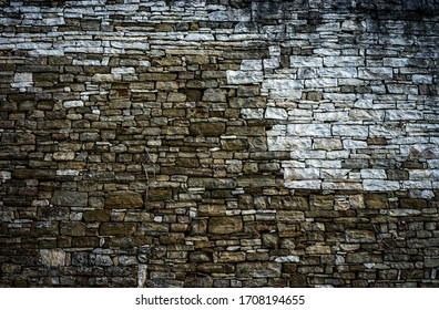 Wall made of many small rocks with color variance.