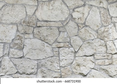 Wall made of natural limestone. Irregular stone surface