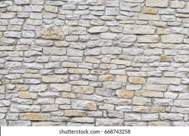 Wall made of natural limestone.Irregular stone surface.