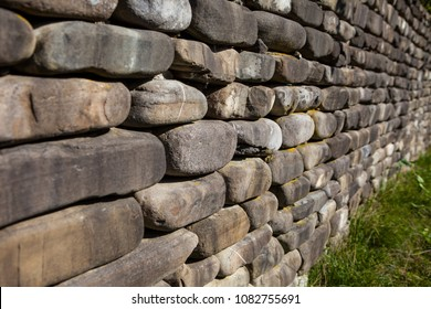 The wall is made of natural rounded sandstone stone of gray color. Concept Black Sea masonry.