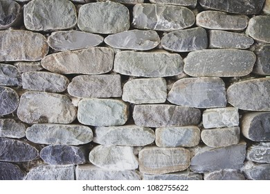 The wall is made of natural sandstone from a gray color. The concept of the Black Sea masonry