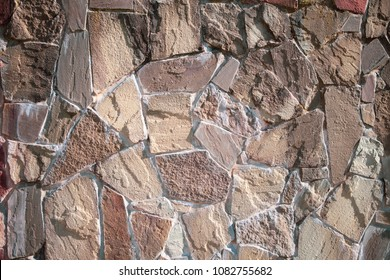 The wall is made of natural sandstone from a gray color. The concept of the Black Sea masonry.
