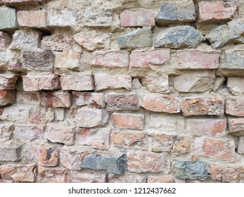 A wall made of old broken bricks, very destroyed bricks.