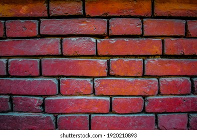 the wall is made of old red brick. Dark red background.
