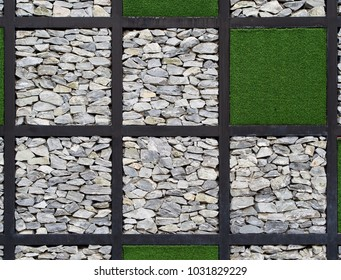 The wall is made of steel black frame decorated with stones and artificial grass, Background texture