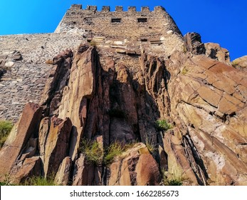 Wall of a medieval Ankara Castle (Turkey) on a rock - bottom view. Beautiful vintage background of cliff and ancient stone building, with copy space