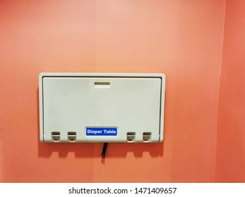 Wall mounted baby changing diaper station on orange concrete wall in public restroom.