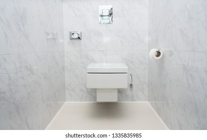 Wall mounted minimalist toilet or WC in luxury tiled bathroom with push button flush