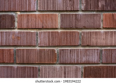 Wall of new building made with rows of rectangle red color bricks connected with concrete mix at bright light close view