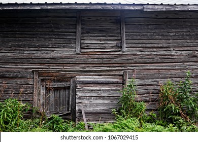 The wall of an old abandoned barn house has been built with three closed holes. I wonder what they are for.