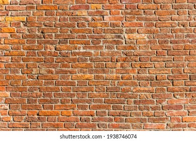 A wall of old, cracked bricks, with a weathered and faded surface. Restored brickwork of an old house.