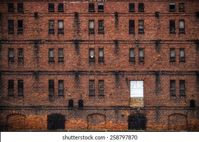 wall of the old factory building of red brick with narrow windows