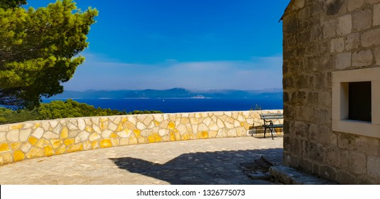 Wall of old typical mediterranean church of white stone situated on the top of the hill of the island Mljet and surrounded by bright green trees, hot sunny summer day with blue sky, Croatia