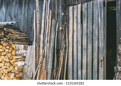 A wall of an old wooden shed. Birch firewood, boards and trees stacked next to him. Doors open. Vintage.