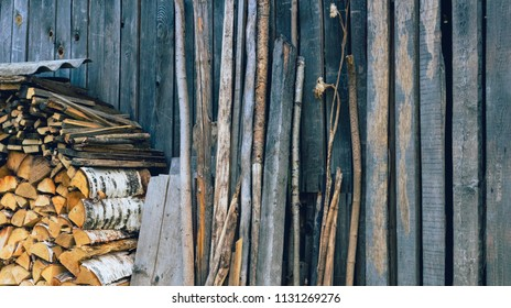 A wall of an old wooden shed. Birch firewood, boards and trees stacked next to him. Vintage