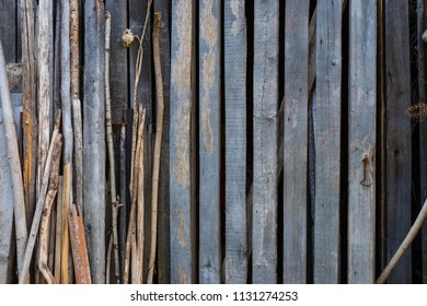 A wall of an old wooden shed, boards and trees stacked next to him.