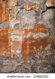 A wall of painted plaster that has worn away to expose bricks