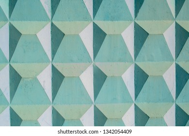 The wall is painted in turquoise with relief squares, triangles, trapezoids