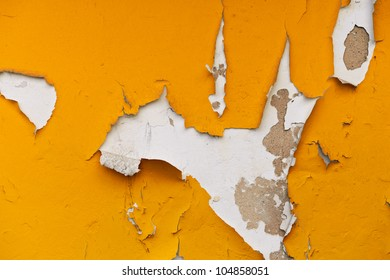 A wall with peeling plaster orange color.