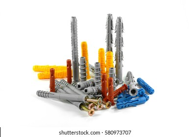 Wall plug - also known as screw anchor or dowel, in different colors and sizes on one pile, isolated on white, plastic tool