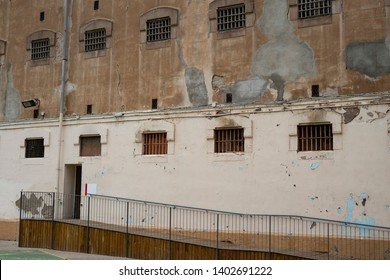 Wall of prison building with access ramp. Wall with windows with bars of prison cells.