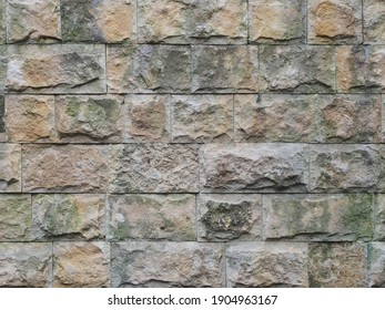 Wall with a rough textured cladding of spotty rectangular tiles. Not seamless texture