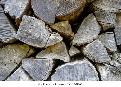 Wall of rugged textured firewood logs stacked in a rural Maine wood shed.